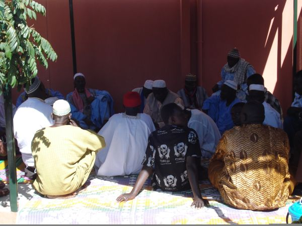1i: Our village Alkalo, the local Imam, the elders of Tujereng and our staff joined together to officially bless and pray for the success of our business before opening in 2009. They are seated under the solar panel canopy.