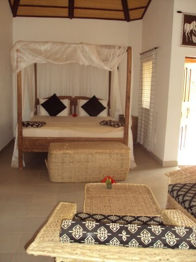 2b: one of the 4 lodges showing the 4-poster bed withmosquito drapes. This was made by a local carpenter.You can also see Baba's woven hampers, chairs and table.All rooms are furnished in the same way.