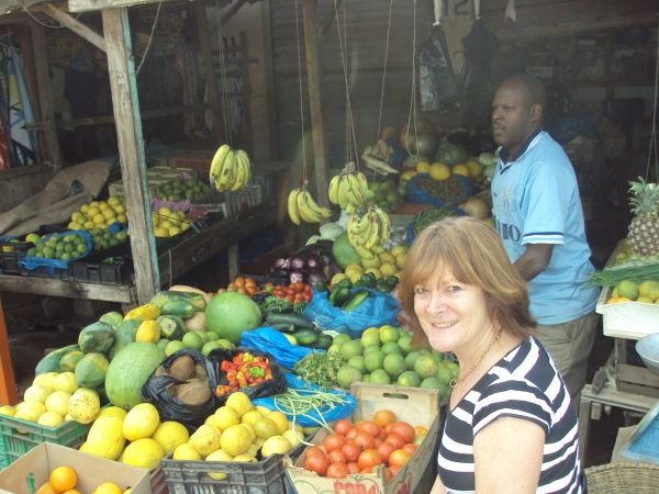 2p: Here I am at the local fruit and veg market (where Buba always gives me a seat!) while he completes my order. Much of it comes from larger producers (up-river) in The Gambia. Other produce, such as salads, I buy more locally.