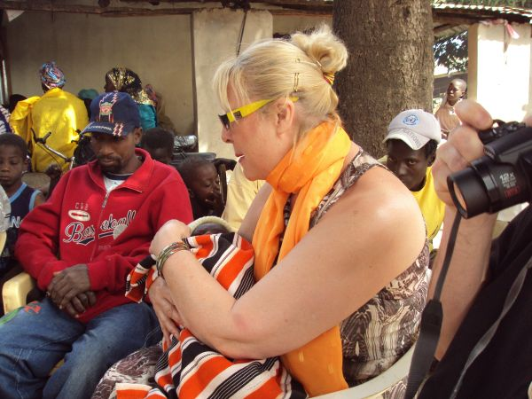 5b: Here is one of our guests at a naming ceremony held in a neighbouring compound. She was very keen to go and was welcomed by the parents who wanted her to hold the baby.