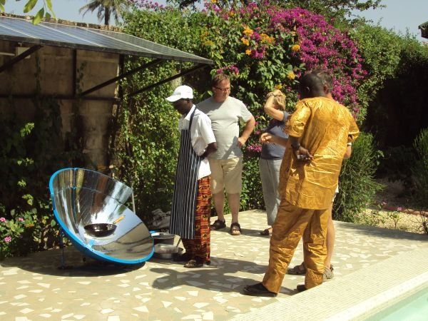 5f: The solar cooker is being demonstrated to the village Alkalo (mayor) and some other guests, who were all curious to know how it worked and whether other local kitchens might adopt this method in future.
