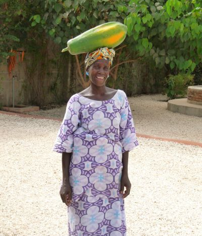5i: Mariama (our laundry lady) is bringing a papaya from her garden to sell to us for use in the restaurant.