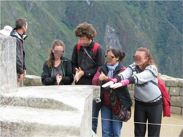 Tourists at the Hitching Stone in Machu Picchu